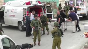 جندي إسرائيلي يمر بجانب منفذ الهجوم الفلسطيني منزوع السلاح والملقى على الأرض قبل لحظات من قيام جندي آخر بإطلاق النار عليه في الرأس بعد هجوم طعن في الخليل في 24 مارس، 2016. (لقطة شاشة: بتسيلم)