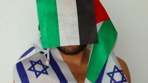 """خضر ابو سيف مع اعلام متناقضة، ضمن سلسلة """"الاحتفال"""" للمصور خافيير كلاين (Courtesy Xavier Klaine)"""