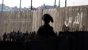 جندي اسرائيلي يراقب فلسطينيين يمرون حاجز قلنديا متجهين نحو القدس (Issam Rimawi/Flash90)