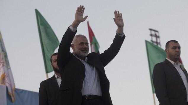 قائد حماس إسماعيل هنية يلوح للجمهور خلال مسيرة مناهضة لإسرائيل في 26 فبراير، 2016، في مدينة غزة جنوبي قطاع غزة. (AFP/Said Khatib)