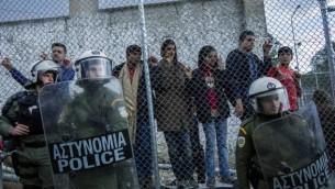 الشرطة اليونانية تقف أمام مخيم موريا خلال تظاهرة للاجئين ضد الإتفاق الجديد بين الإتحاد الأوروبي وتركيا، 24 مارس، 2016 في جزيرة لسبوس اليونانية. (AFP/Fabio Bucciarelli)