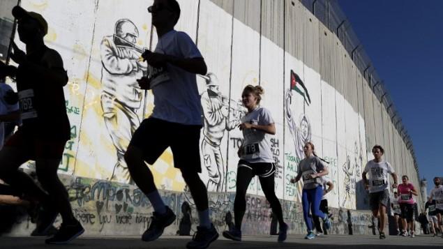 عداؤون يركضون بجانب الجدار الفاصل الإسرائيلي في مدينة بيت لحم في الضفة الغربية خلال ماراثون فلسطين الرابع، 1 أبريل، 2016. (AFP/Thomas Coex)