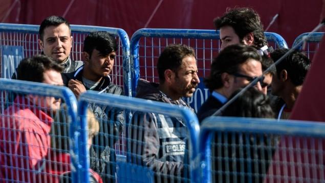 ضابط شرطة يرافق مهاجر مرحل من سفينة صغيرة تحمل مهاجرين تم ترحيلهم الى تركيا، 4 ابريل 2016 (OZAN KOSE / AFP)