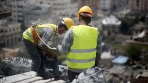 عمال فلسطينيون يزيلون الحطام من مبنى في غزة دمر خلال حرب 2014 بين حماس واسرائيل، 5 ابريل 2016 (MOHAMMED ABED / AFP)
