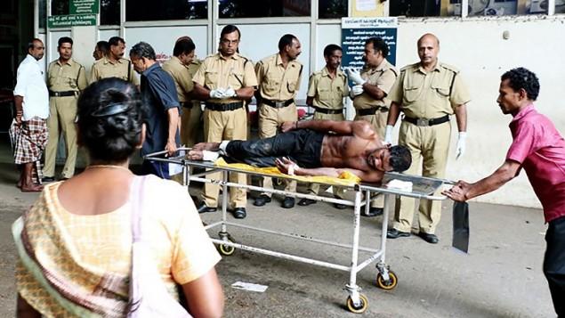 طواقم انقاذ هندية تنقل رجل مصاب في حريق وقع داخل معبد هندوسي في جنوب الهند، 10 ابريل 2016 (STR / AFP)