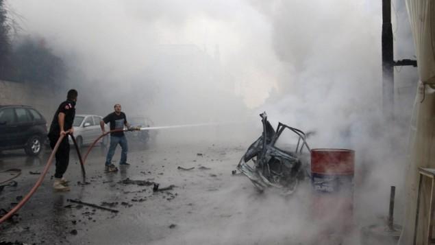 طواقم الطوارئ اللبنانية  تقوم بإطفاء النار المشتعلة بعد انفجار سيارة مفخخة في مدينة صيدا الجنوبية، 12 أبريل، 2016. (AFP PHOTO / MAHMOUD ZAYYAT)