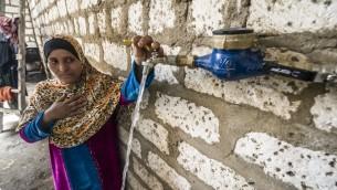 الوالدة المصرية أعز منهم تقف امام الصنبور الموجود الان في فناء منزلها، 23 ابريل 2016 (KHALED DESOUKI / AFP)