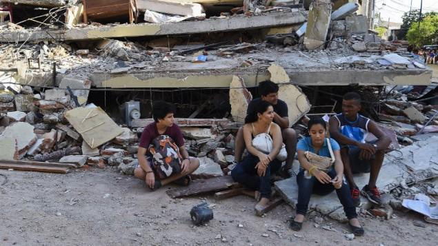 مشردون يرتاحون  أمام منزل دمر في مانتا، الإكوادور،  17 أبريل 2016 يوم بعد احد ا قوى الزلازل وصلت قوته 7.8 درجة اسفر عن 246 قتيلا و 2527 جريحا. AFP PHOTO / LUIS ACOSTA