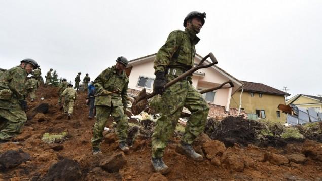 قوات الدفاع الذاتى البرية في اليابان خلال البحث عن الضحايا دفنوا في انهيار أرضي بسبب الزلزال الاخير في قرية مينامي آسو في مقاطعة كوماموتو 18 نيسان،  2016 KAZUHIRO NOGI / AFP
