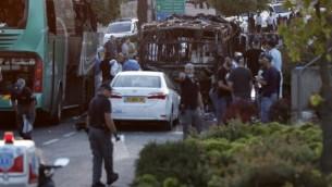قوى الأمن الإسرائيلية تحقق في موقع انفجار الحافلة جنوبي القدس، 18 ابريل، 2016. (Thomas Coex/AFP)