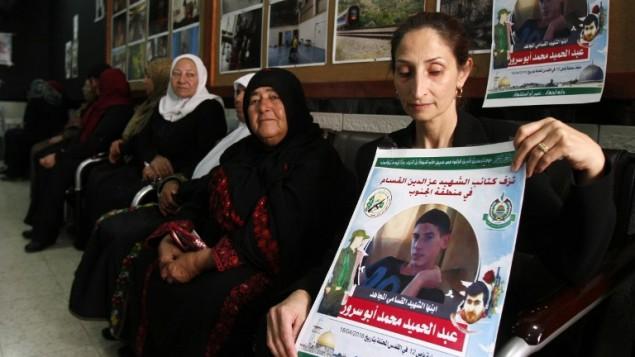 """ازهار ابو سرور، والدة عبد الحميد ابو سور (19 عاما) الذي قام بتنفيذ الهجوم الإنتحاري في 18 ابريل في حافلة رقم 12 في حي """"تل بيوت"""" في القدس، تحمل ملصق عليه صورته في مخيم عايدة في الضفة الغربية، 22 ابريل 2016 (AFP PHOTO / MUSA AL SHAER)"""