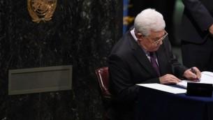 رئيس السلطة الفلسطينية محمود عباس يوقع على أوراق خلال مراسم التوقيع على اتفاق باريس التاريخي في قاعة الجمعية العامة للأمم المتحدة في 22 أبريل، 2016. (AFP PHOTO/TIMOTHY A. CLARY)