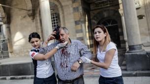 عمال اغاثة يساعدون رجل مصاب بعد يقوط صواريخ في مسجد على مدينة كيليس التركية، 24 ابريل 2016 (YASIN AKGUL / AFP)