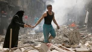 اشخاص بين الحطام بعد غارة في مدينة حلب السورية التي تسيطر عليها المعارضة، 28 ابريل 2016 (AFP/ AMEER ALHALBI)