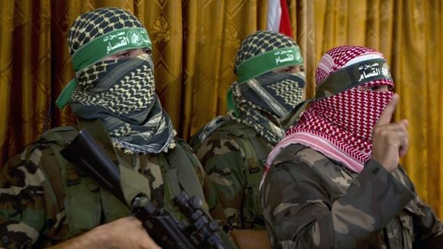 أبو عبيدة (من اليمين)، المتحدث الرسمي للجناح العسكري لحركة حماس، كتائب عز الدين القسام، في مؤتمر صحفي في 3 يوليو، 2014، في مدينة غزة. (AFP/Mohammed Abed)