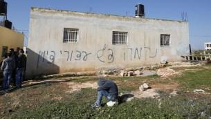 """شعار غرافيتي رُسم على جدار منزل في الضفة الغربية في قرية بيتللو، 22 ديسمبر، 2015. وحمل الشعار عبارة، """"الإنتقام، تحية من أسرى صهيون"""" (AFP PHOTO/ABBAS MOMANI)"""
