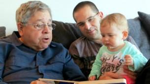 ريتشارد ليكين (من اليسار) يقرأ كتابا لحفيدته وإلى جانبه يجلس نجله ميخا أفني. يناير 2014. (Courtesy)