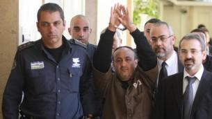 مروان البرغوثي، القيادي في حركة فتح، تصطحبه الشرطة الإسرائيلية إلى قاعة المحكمة المركزية في القدس للإدلاء بشهادته في دعوى مدنية أمريكية ضد القيادة الفلسطينية، في يناير 2012. (Flash90)