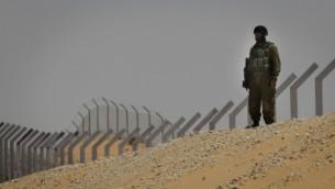 جندي إسرائيلي يقف بالقرب من قسم من السياج المبني حديثا على طول الحدود، مع شبه جزيرة سيناء في الخلفية. (Tsafrir Abayov/Flash 90)
