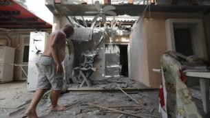 رجل يتفقد منزل لحقت به أضرار يعد سقوط صاروخ أطلقه مسلحون من قطاع غزة في بلدة جنوبي إسرائيل، 24 أكتوبر، 2014. ( Tsafrir Abayov/Flash90)