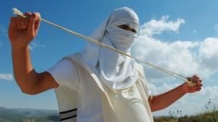 صورة توضيحية لمستوطن يهودي ملثم يحمل مقلاعا وهو يقف بالقرب من مستوطنة متسبيه يتسهار في الضفة الغربية، 19 مايو، 2013. (Mendy Hechtman/Flash90)
