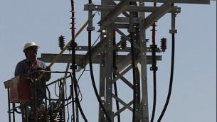 صورة توضيحية لعامل صيانة في شركة الكهرباء يعمل على خطوط الكهرباء (Flash 90)