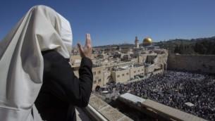 مصلون يهود يغطون رؤوسهم بشالات صلاة خلال صلاتهم أمام حائط المبكى في البلدة القديمة في القدس، خلال عيد الفصح، 6 أبريل، 2015. (Yonatan Sindel/Flash90)