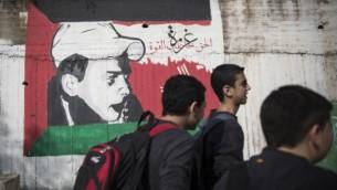 فتية في طريقهم إلى البيت من المدرسة يمرون إلى جانب رسم لمحمد أبو خضير، الفتى الفلسطيني الذي قُتل على يد متطرفين يهود، مع العلم الفلسطيني، في شارع مركزي شمال إسرائيل. (Hadas Parush/Flash90)