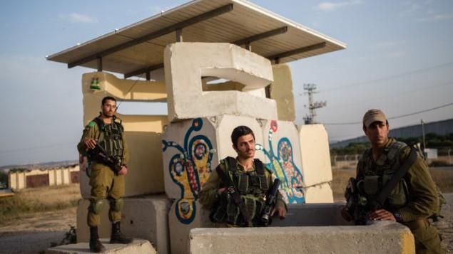 جنود اسرائيليون يحرسون موقع عسكري في كيبوتس 'نتيف هعسارا, في 5 ابريل 2016 (Corinna Kern/Flash90)