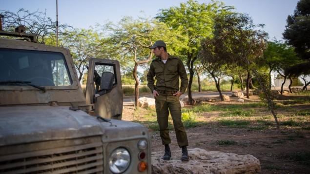 جندي إسرائيلي يقف إلى جانب مركبة عسكرية بالقرب من حدود شمال قطاع غزة في 7 أبريل، 2016. (Corinna Kern/FLASH90)