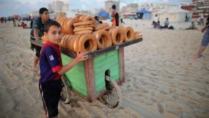 اطفال يبيعون الخبز على شاطئ غزة، 13 يونيو 2015 (Christopher Furlong/Getty Images via JTA)