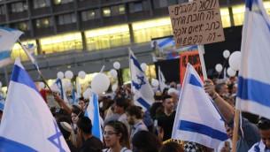 يتجمع متظاهرون في ميدان رابين في تل ابيب في 19 ابريل 2016 دعما للجندي الور عزريا المتهم بإطلاق النار على معتدي فلسطيني عاجز في الخليل. المتابة على اللافتة: 'القضاء على الارهابيين - هذا واجب الجندي. المحاكمة على ذلك - هذه الجريمة' (Judah Ari Gross/Times of Israel staff)