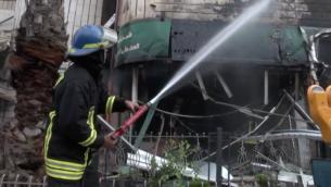 """عنصر من قوات الاطفاء التابعة للدفاع المدني الفلسطيني يقوم باخماد الحريق الذي اندلع في اعقاب """"عملية تفجير محكمة للخزنة"""" في مصرف في رام الله  14 ابريل 2016 (صورة شاشة, يوتوب)"""