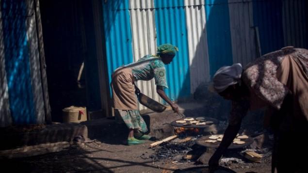 أكثر من 20 سيدة يهودية أثيوبية يقمن بإعداد خبز المصة على النار في غوندار، إثيوبيا في 20 أبريل، 2016. تتلقى هؤلاء السيدات أجرا صغيرا في نهاية الأسبوع. (Miriam Alster/Flash90)