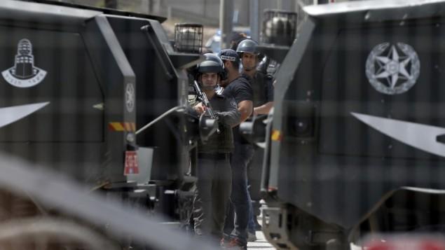 قوات أمن إسرائيلية تقف عند حاجز قلنديا القريب من رام الله في الضفة الغربية بعد أن قام حارس أمن بإطلاق النار على فلسطينيين عن الحاجز في 27 أبريل، 2016، بعد أن قام أحدهما بإلقاء سكين على حراس الحدود. (AFP/Abbas Momani)