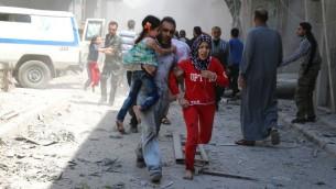 عائلة سوريا تحاول الوصول الى مأوى وسط الحطام بعد غارة جوية في مدينة حلب السورية الشمالية، 29 ابريل 2016 (AMEER ALHALBI / AFP)