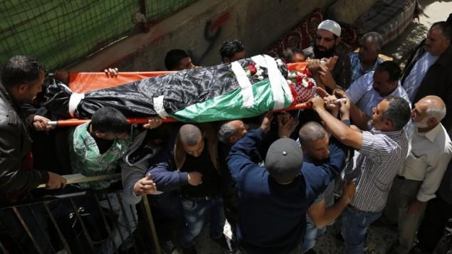 مشيعون يحملون جثمان الفلسطيني أحمد شحادة (36 عاما) خلال جنازته في بيتونيا، بالقرب من مدينة رام الله، 4 مايو، 2016. (AFP PHOTO / ABBAS MOMANI)