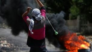 متظاهر فلسطيني يلقي بحجارة مستخدما مقلاعا باتجاه قوات الأمن الإسرائيلية خلال موجهات في 6 مايو، 2016. (AFP PHOTO / JAAFAR ASHTIYEH)