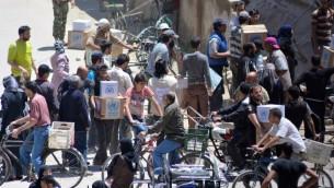 فلسطينيون وسوريون يتلقون رزم مساعدات من وكالة اونروا في مخيم اليرموك جنوب دمشق، 12 مايو 2016 (RAMI AL-SAYED / AFP)
