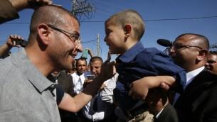 الصحافي الفلسطيني محمد القيق الذي اضرب عن الطعام لاكثر من ثلاثة اشهر احتجاجا على اعتقاله الاداري، يعانق طفله عند وصوله بلدته، دورا، في الضفة الغربية بعد اطلاق سراحه، 19 مايو 2016 (HAZEM BADER / AFP)