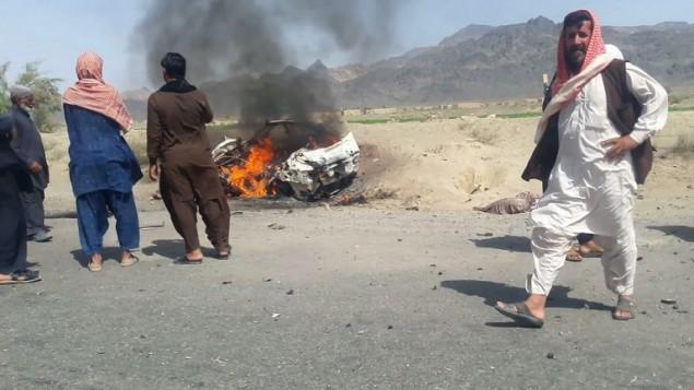 سكان محليون باكستانيون يحتشدون حول مركبة مدمرة تعرضت لهجوم من قبل طائرة بدون طيارة يُتقد بأن زعيم حركة طالبان الأفغانية الملا أختر منصور كان فيها في بلدة أحمد وول النائية في إقليم بلوشيستان، 21 مايو، 2016. (AFP)