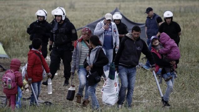 عائلة تحمل اغراضها اثناء عملية اخلاء الشرطة لمخيم ايدوميني على الحدود اليونانية المقدونية، 24 مايو 2016 (YANNIS KOLESIDIS / POOL / AFP)