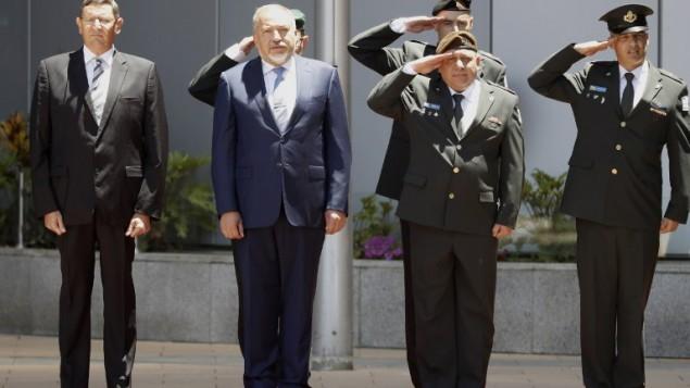 وزير الدفاع الجديد أفيغدور ليبرمان (الثاني من اليسار) ورئيس هيئة الأركان العامة غادي آيزنكوت (الثاني من اليمين) يستمعان إلى النشيد الوطني الإسرائيلي خلال مراسيم الترحيب بليبرمان في وزارة الدفاع في تل أبيب، 31 مايو، 2016. (AFP PHOTO / JACK GUEZ)