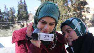ناشطتان فلسطينيتان في منظمة بتسيلم لحقوق الانسان تستخدمان كاميرا لتوثيق نشاطات الحش والمستوطنين الإسرائيليين في الضفة الرغبية، 2014 (B'Tselem/CC BY 4.0)