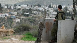 صورة توضيحية لجندي إسرائيلي يقوم بحراسة مستوطنة كدوميم، مع قرية قدوم الفلسطينية في الخلفية، 13 نوفمبر، 2009. (Gili Yaari/Flash90)