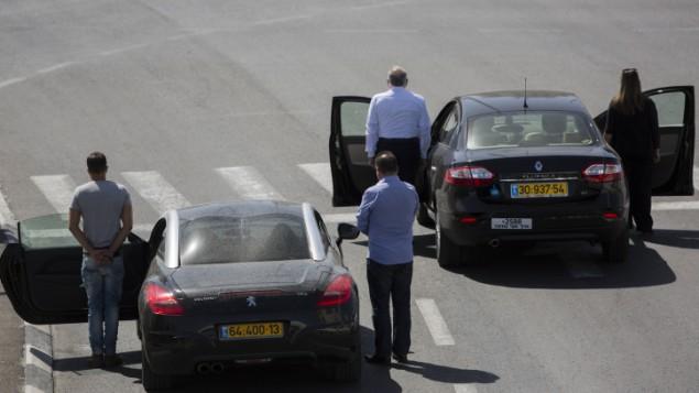 إسرائيليون يقفون إلى جانب مركباتهم عند مدخل مدينة القدس مع سماع صفارات الإنذار لإعلان الوقوف دقيقتي صمت لإحياء ذكرى المحرقة في جميع أنحاء البلاد، 28 أبريل، 2014. (Yonatan Sindel/Flash90)