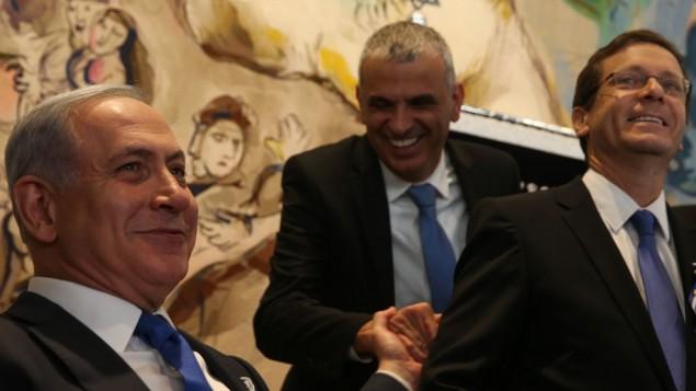 """رئيس الوزراء بينيامين نتنياهو (من اليسار) يصافح رئيس حزب """"كولانو"""" موشيه كحلون (الوسط) خلال الجلسة الإفتتاحية للكنيست ال20 في 31 مارس، 2015. من اليمين رئيس حزب """"المعسكر الصهيوني"""" يتسحاق هرتسوغ. (Nati Shohat/Flash90)"""