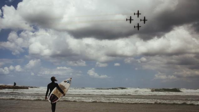 راكب امواج يشاهد عرض سلاح الجو الإسرائيلي خلال احتفالات يوم استقلال اسرائيل ال67 في شاطئ تل ابيب، 23 ابريل 2015 (Matanya Tausig/Flash90)
