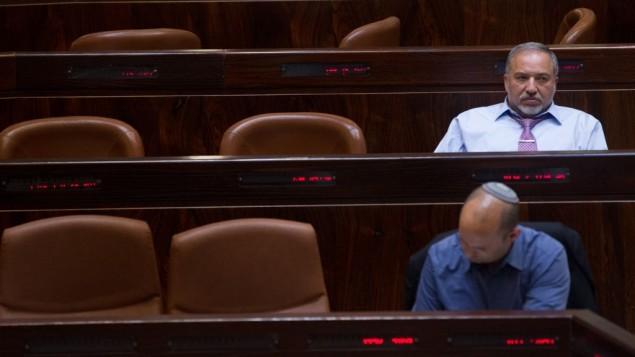 """رئيس حزب """"إسسرائيل بيتنا"""" أفيغدور ليبرمان (من الخلف) ورئيس الحزب """"البيت اليهودي"""" نفتالي بينيت (من الأمام) خلال جلسة في الكنيست، 11 مايو، 2015. (Miriam Alster/Flash90)"""