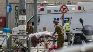مسعفو الجيش الإسرائيلي يقومون بإخلاء جثة شاب فلسطيني عند حاجز قلنديا بعد محاولة طعن مزعومة، 27 أبريل، 2016. (Yonatan Sindel/Flash90)
